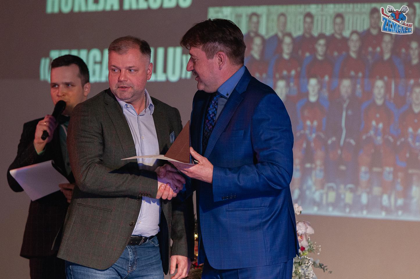 Divi vīrieši spiež viens otram rokas, fonā vīrietis runā mikrofonā