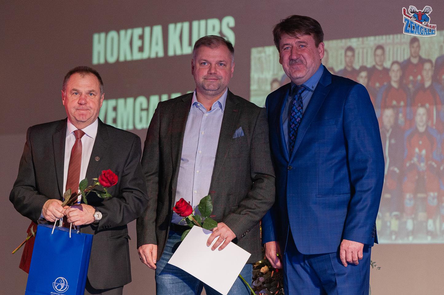 Trīs vīrieši stāv ar puķēm un maisiņu rokās