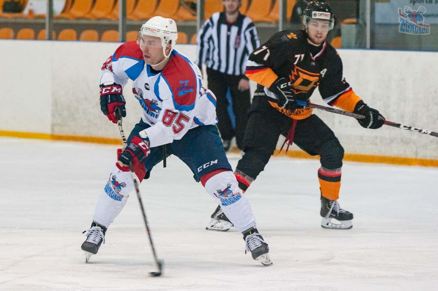 Hokeja uzbrucējs ar pretinieku fonā