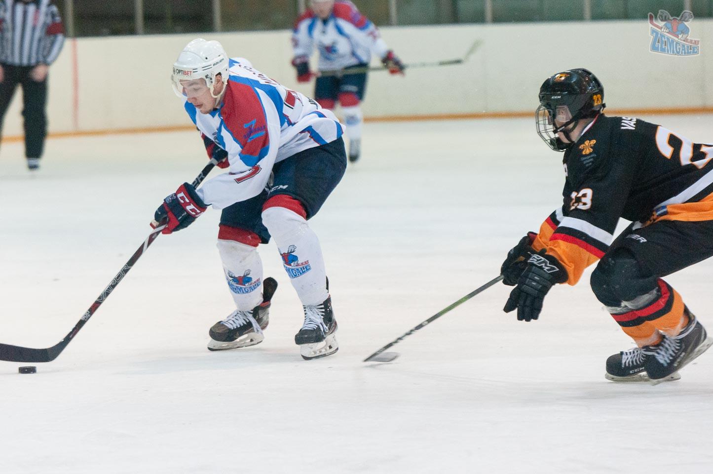 Hokeja uzbrucēj uzbrukumā ar ripu