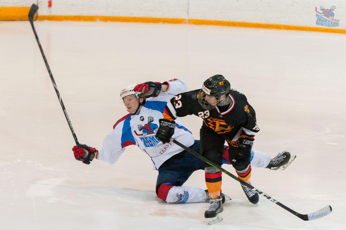 Hokeja aizsargs ar spēka paņēmienu nogāž pretinieka uzbrucēju