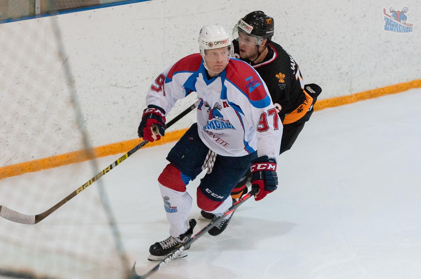 Hokeja uzbrucējs ar pretinieka aizsargu aizmugurē