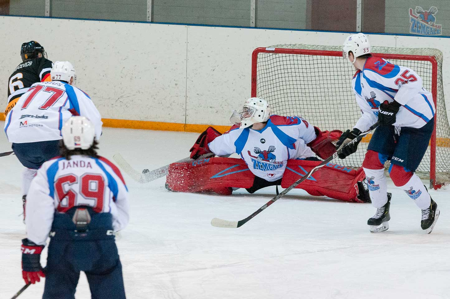 Hokeja vārtsargs nosēžas špagatā, lai atvairītu ripu