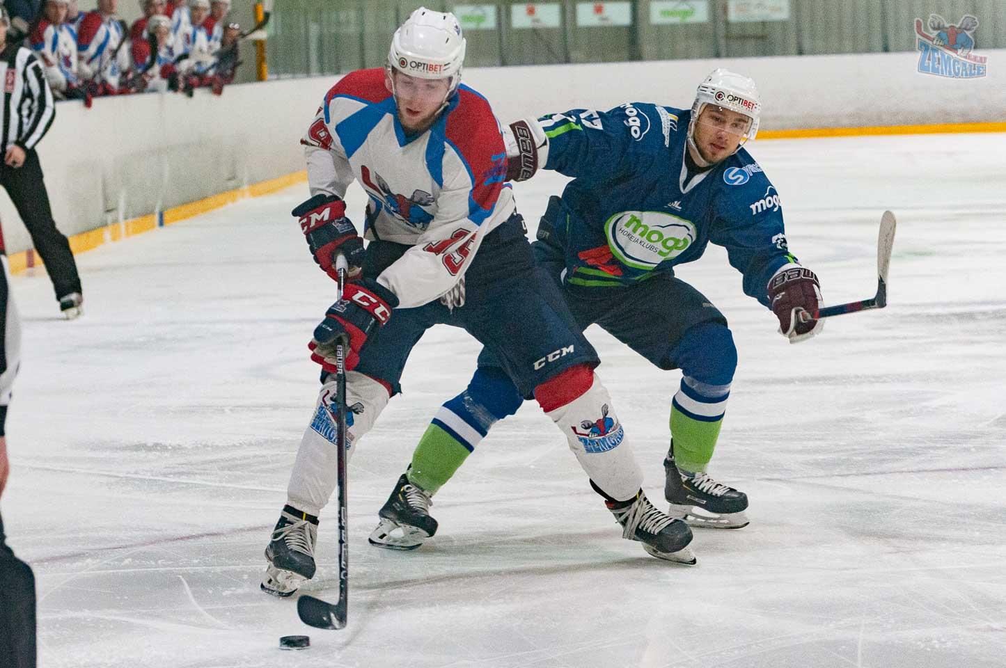 Hokeja uzbrucējs apsteidz pretinieku, kurš slido ar pacelto nūju