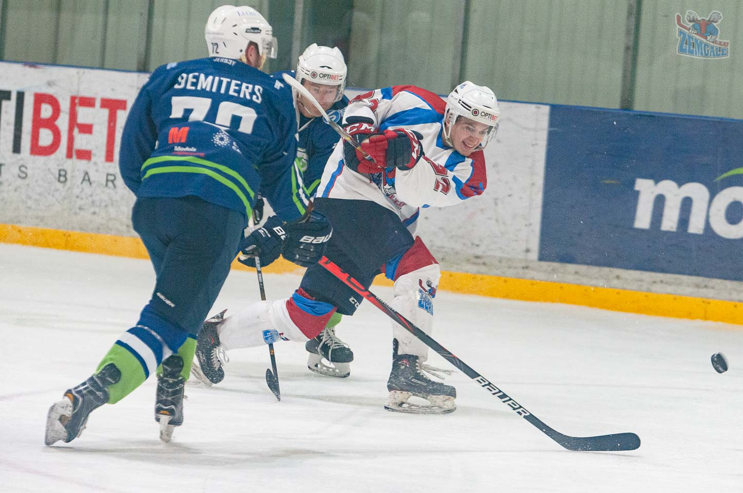 Hokeja uzbrucējs izdara metienu divu spēlētāju ielenkumā