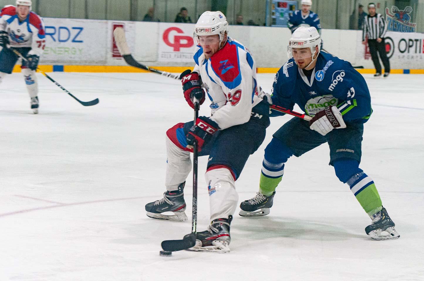 Divu hokeja uzbrucēju cīņā par ripu