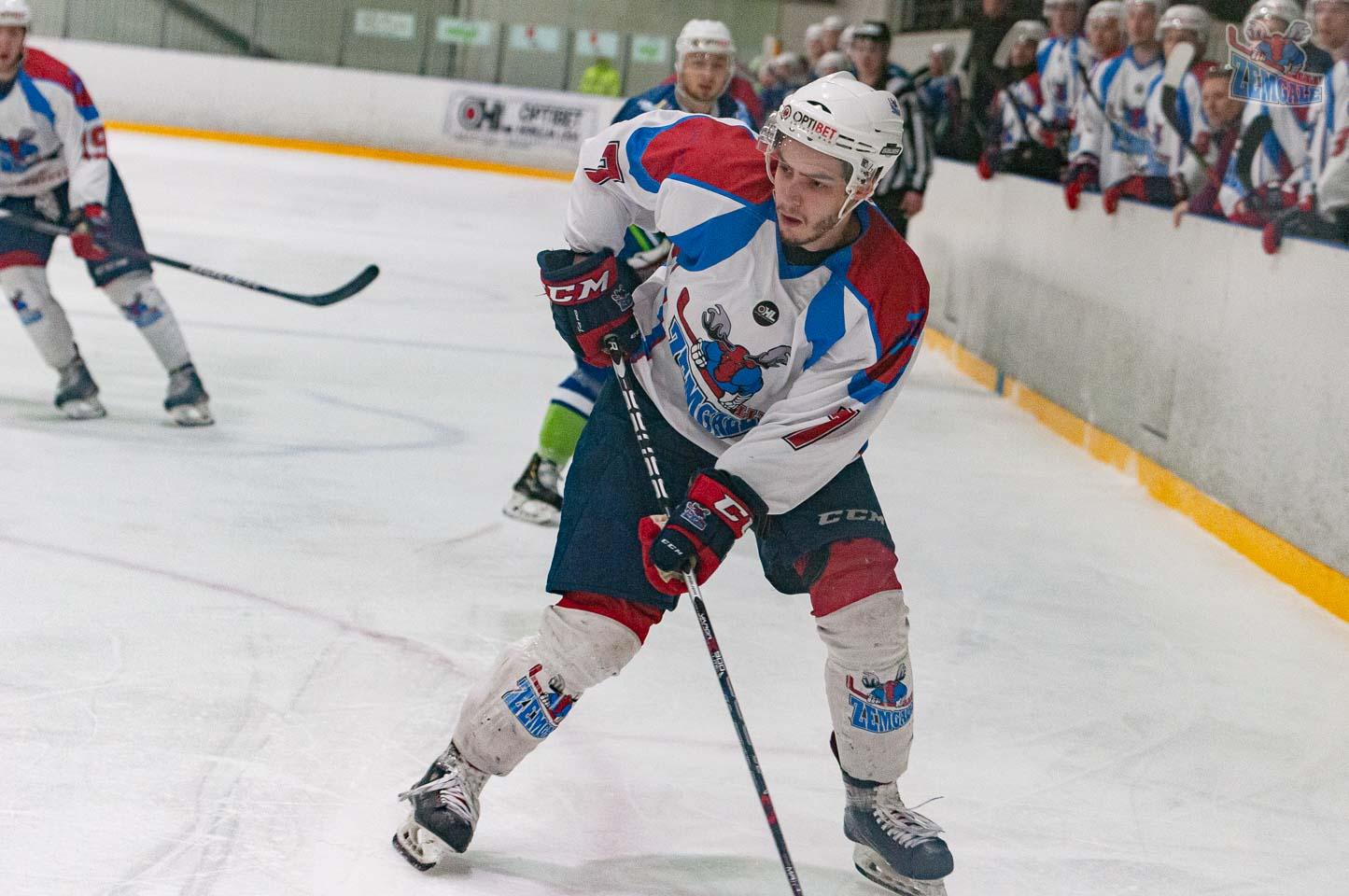 Hokeja uzbrucējs kura slidojumu aizmugurē vēro komanda no soliņa