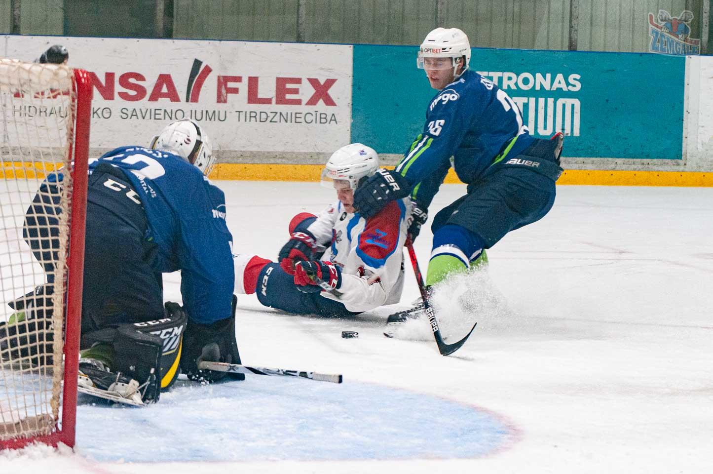 Aizsarga nogāž hokeja uzbrucēju vārtu priekšā