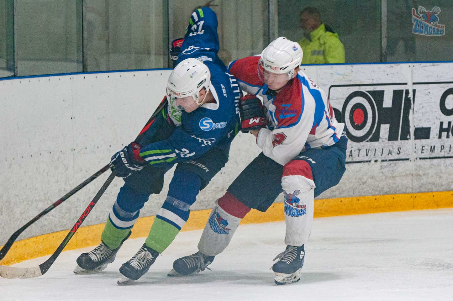 Hokejists mēģina atņemt ripu pretiniekam
